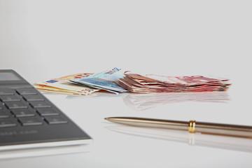 Euroscheine mit Taschenrechner und Kugelschreiber