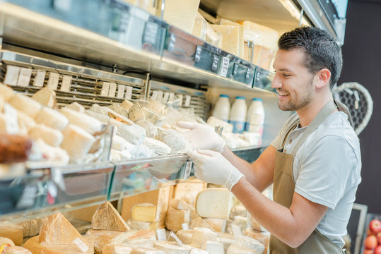 Shop assistant restocking cheese aisle