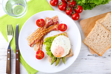 Dish of asparagus with bacon and egg in plate on table, top view