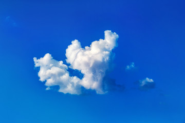 tranquil fluffy white cloud at a blue summer sky background.