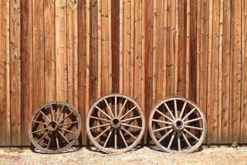 Old wagon wheels lean against a wooden barn
