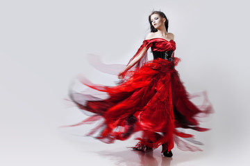 Fashion photo of young magnificent woman in red dress. Studio