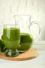 Healthy green smoothie with spinach on wooden table on white wall background
