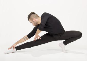 Male dancer practising , arm extented, legs extended.