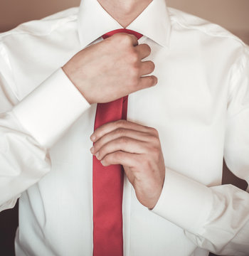 The groom in a white shirt correcting tie