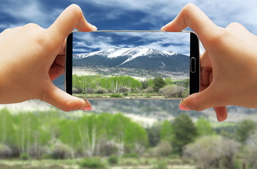 Hand taking photo with smartphone of snowcapped mountain and aspen trees