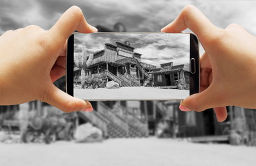 Hand taking photo with smartphone of Wild west cowboy town in black and white