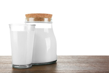 Jar and glass of milk on wooden table, on white background