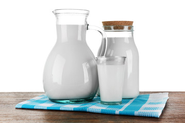 Pitcher, jar and glass of milk on wooden table, on white background