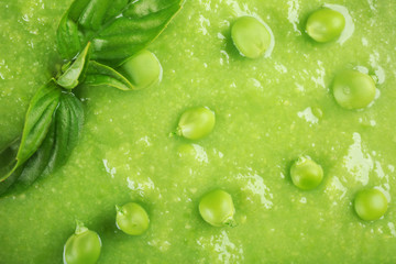Tasty peas soup with basil close up