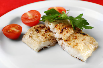 Dish of fish fillet with parsley and tomato on plate close up