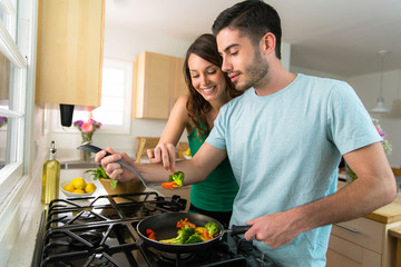 Young attractive couple preparing dinner on a date saving money by cooking at home