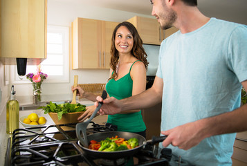 Playful lifestyle cooking at home man and woman flirting and in love