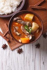 Thai beef massaman curry and rice side dish. vertical top view