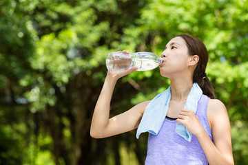 Sporty girl drink water after running
