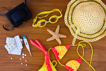 Summer beach accessories and medicine on the table. The concept of medication required in the journey