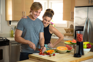 Happy young man and woman prepare a healthy recipe raw vegan lifestyle blonde handsome