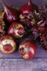 Red beets with lettuce on wooden table close up