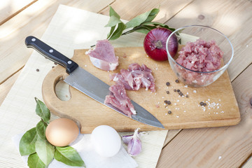 Raw chopped pork tenderloin with herbs in a glass bowl on a wooden board, selective focus