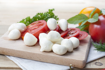 Sliced tomatoes, basil and mozzarella cheese on a wooden board, selective focus