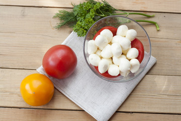Mozzarella cheese in a glass bowl, tomatoes, sliced tomatoes and herbs on a wooden table, selective focus