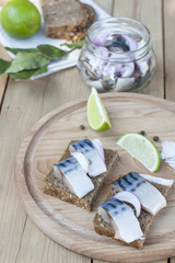 Slices of marinated mackerel with onion in a jar, lime, laurel and bread on wooden board, selective focus