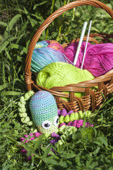 Basket with skein and knitting toy little octopus, selective focus