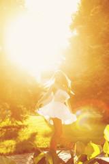 Boho Girl dancing barefoot in park.
