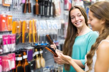 girl buying hairbrush in shopping mall