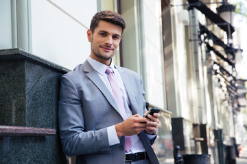 Portrait of a happy businessman holding smartphone