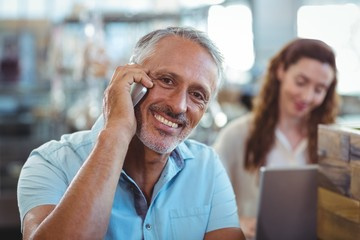 Happy man having phone call and smiling at camera