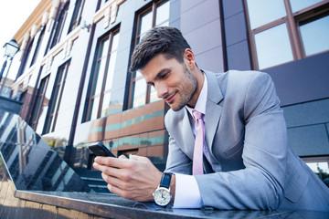 Businessman using smartphone outdoors