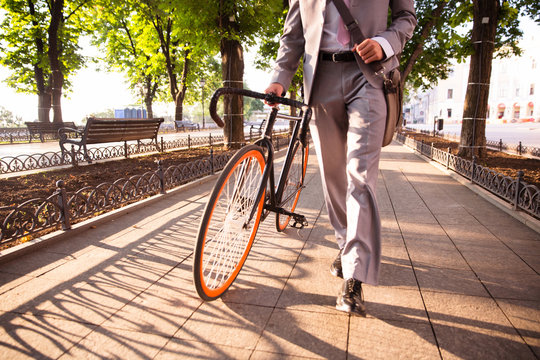 businessman walking with bicycle