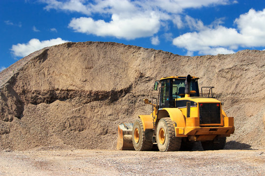 Bulldozer in sand and gravel site with cloudy blue sky