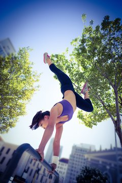 Athletic woman performing handstand on bar