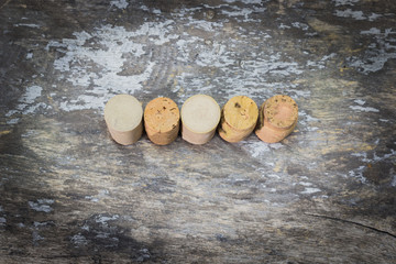 Corkscrew and wine corks on wooden surface
