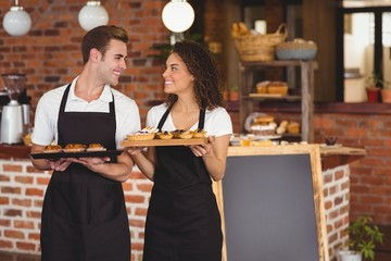 Smiling waiter and waitress holding tray with muffins