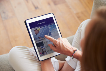 Woman Looking At News App On Digital Tablet