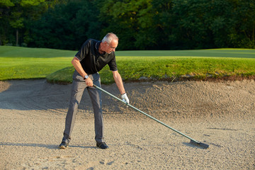 Senior golfer rake the the sand in a bunker