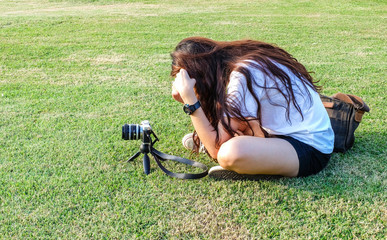 Woman taking a photo on grass background