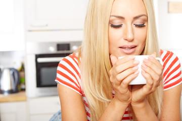 junge blonde frau trinkt morgens kaffee in der küche
