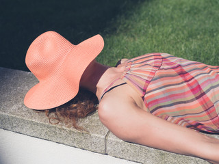 Young woman with hat relaxing outside