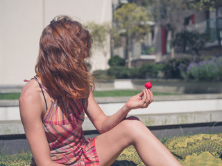 Woman with strawberry outside