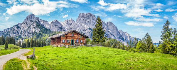 Foto op Canvas Blauw Idyllic landscape in the Alps with mountain chalet and green meadows