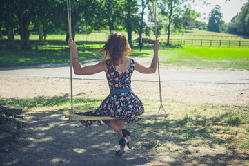 Young woman sitting on a swing