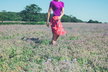 Happy young woman spinning in field of purple flowers