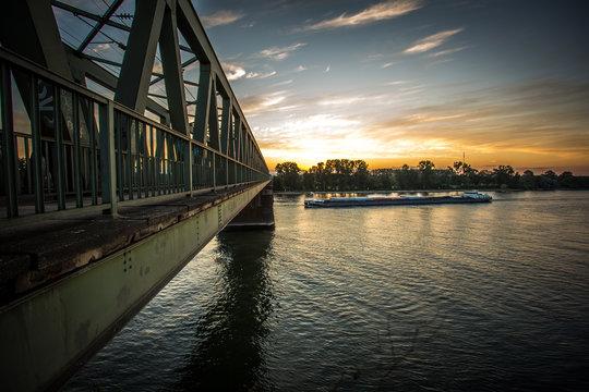 Transportschiff an der Kaiserbrücke am Rhein im Sonnenaufgang
