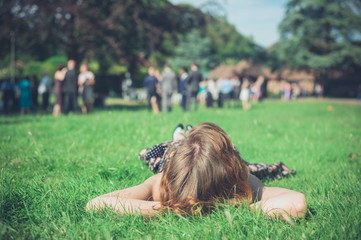 Woman relaxing on grass at party