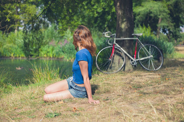 Wall Mural - Young woman relaxing by water in the park