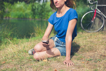 Young woman using smart phone by water in park